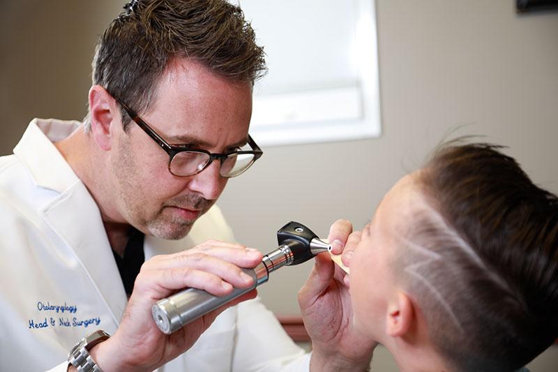 Adam S. Morgan, MD examines a patient's tonsils.