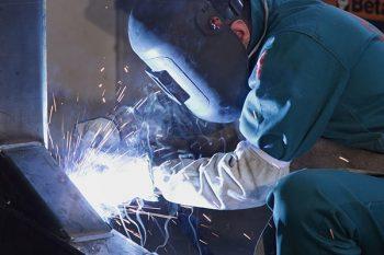 A worker welds a beam