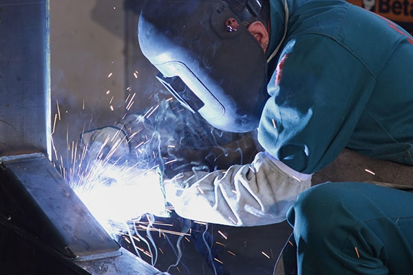 A worker welds a beam