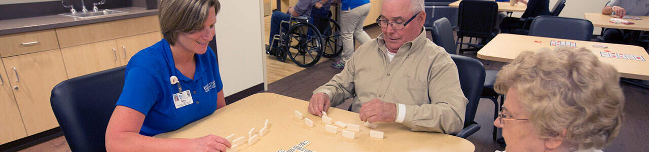 A colleague plays table games with rehab patients