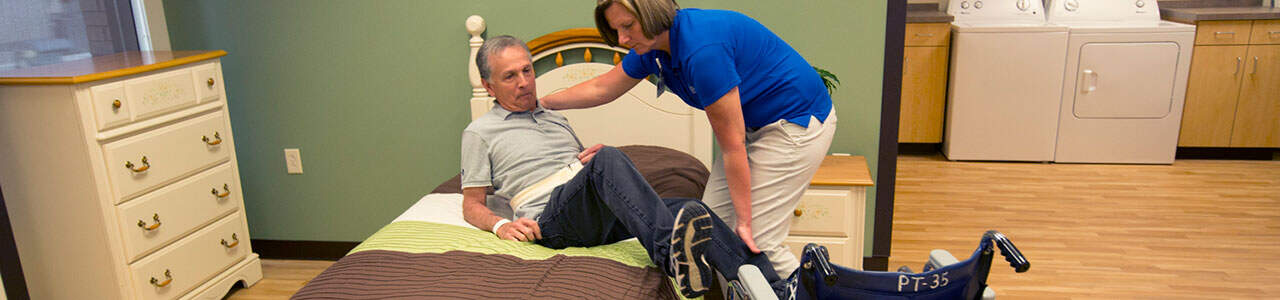 A colleague helps a patient get out of bed.