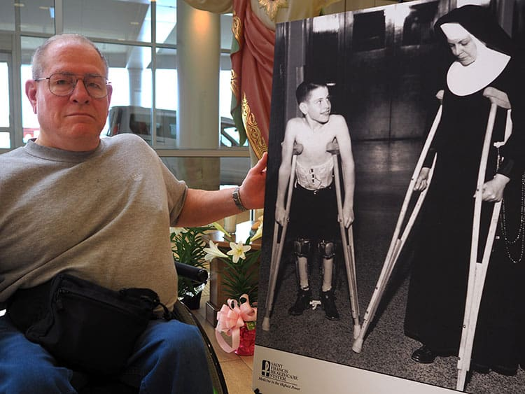 Dave Faris poses with a photo of himself as a boy, when he received treatment for polio at Saint Francis.