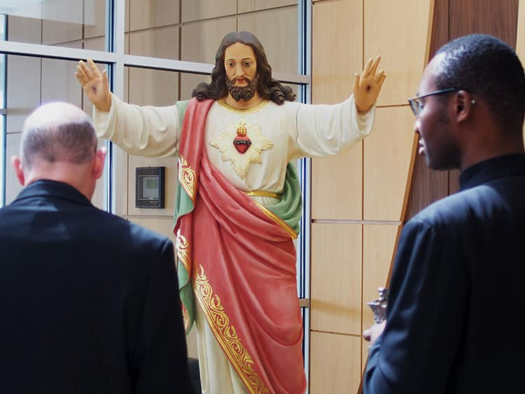 Bishop Edward Rice and Father (Lawrence) Alexander Nwagwu observe the sculpture of the sacred heart of Jesus at the Saint Francis new mission celebration.