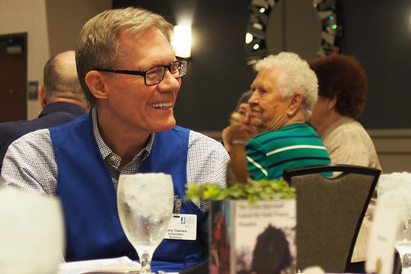Saint Francis volunteer Gary Gaines visits with others during the annual volunteer luncheon.