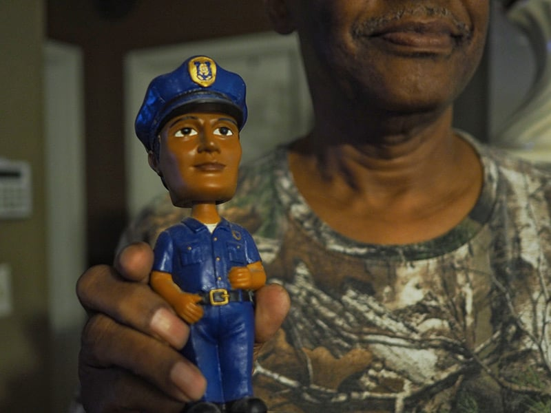 Calvin Box displays his police officer bobblehead. Box is a retired assistant police chief.