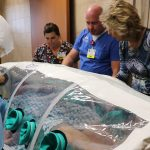 """Gayla Tripp, Infection Prevention & Environmental Services Manager; Chad Garner, Director of Emergency and Trauma Services; and Rep. Kathy Swan look at the """"patient"""" during the Ebola simulation training."""