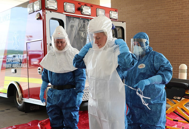 "Cape Girardeau County Ambulance Service workers suit up in order to transport the ""patient"" to a regional Ebola treatment center."