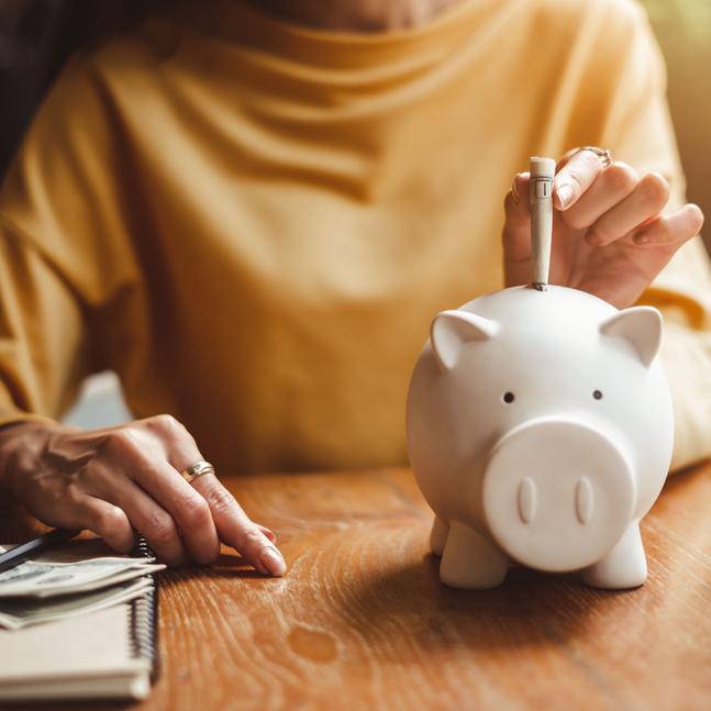 A woman puts a dollar bill into a piggy bank